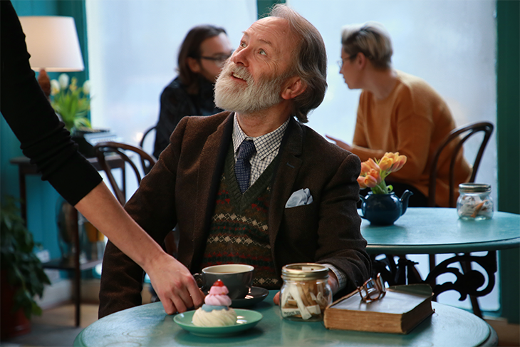 Man with beard at cafe table